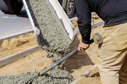 Truck mixer pouring concrete cement into a concrete with sidewalk